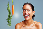 Fresh carrot and young woman laughing against colored background