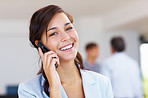 Business woman on cellphone with staff in background