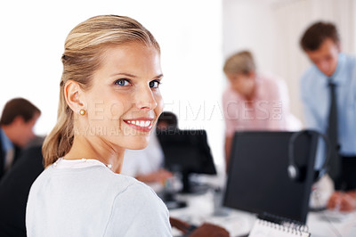 Buy stock photo Portrait of a pretty young businesswoman smiling while working at office with her colleagues