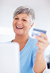Smiling mature woman shopping online