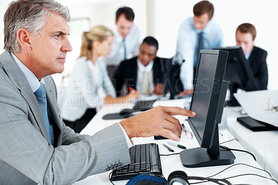 Buy stock photo Portrait of a successful mature businessman working on computer with his team in background