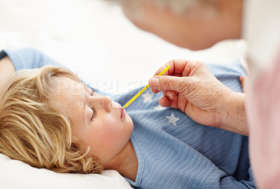 Buy stock photo Portrait of a mature woman checking temperature of sick boy