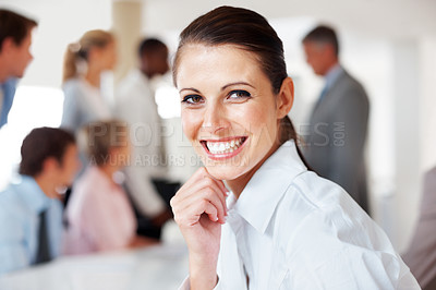 Buy stock photo Closeup portrait of a smiling young businesswoman and her collleagues working behind at office