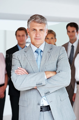 Buy stock photo Portrait of a successful senior manager standing with his hands folded and his team standing behind at office