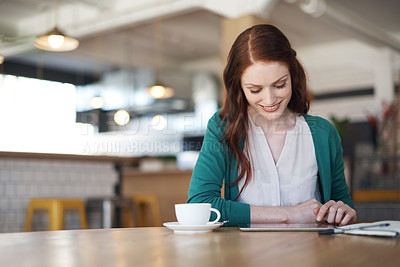 Buy stock photo Shot of a young woman using her digital tablet in a coffee shop