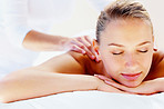 Serene woman receiving a shoulder massage at day spa