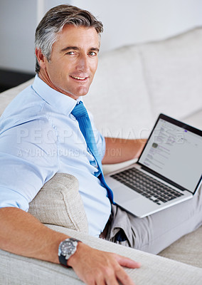 Buy stock photo Portrait of a mature businessman using a laptop while sitting on a sofa