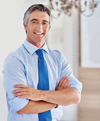Buy stock photo Portrait of a smiling mature businessman standing with his arms crossed