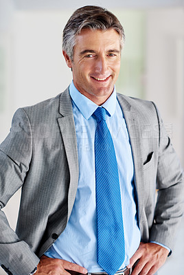 Buy stock photo Portrait of a smiling mature businessman standing with his hands on his hips