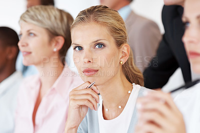 Buy stock photo Serious young female business executive sitting with her colleagues in meeting at office