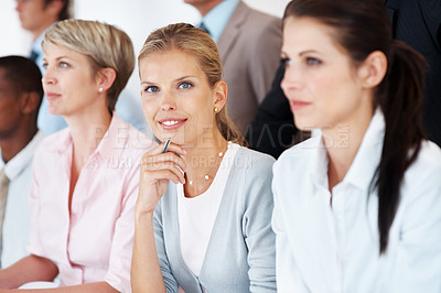 Buy stock photo Portrait of a happy young businesswoman sitting at a meeting amidst her colleagues