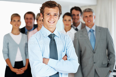 Buy stock photo Portrait of a successful businessman standing with arms crossed and colleagues in background