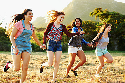 Buy stock photo Shot of a group of friends running through a field together