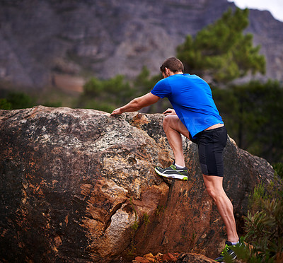 Buy stock photo Rearview shot of a man out stretching before a run in the woods