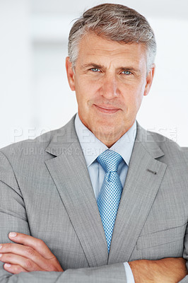 Buy stock photo Portrait of a happy mature businessman in suit standing with arms crossed