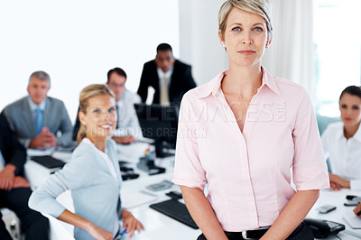 Buy stock photo Portrait of confident attractive businesswoman with her group working in the background