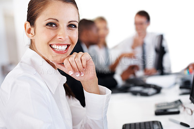 Buy stock photo Portrait of a smiling businesswoman looking confidently with with people working in background