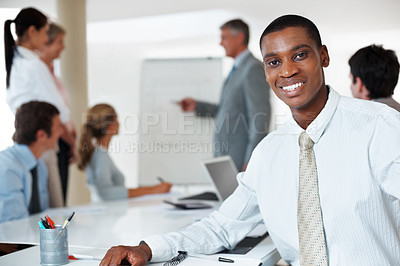 Buy stock photo Portrait of an african american young businessman smiling while attending a presentation at board room