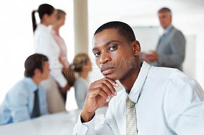 Buy stock photo Serious business man looking at you with colleagues in background during a presentation