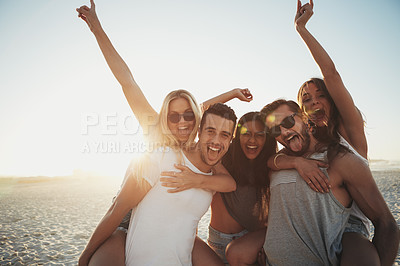 Buy stock photo Shot of a group of young friends enjoying a day at the beach