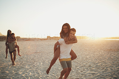 Buy stock photo Shot of two men piggybacking their girlfriends while racing on the beach