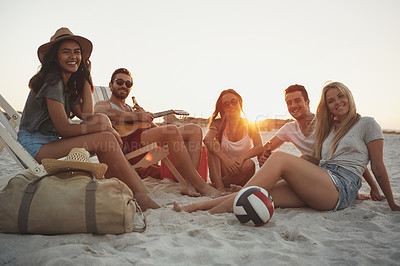 Buy stock photo A group of friends spending time together at the beach with a guitar and a few drinks