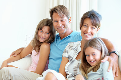 Buy stock photo Family of four sitting together on a sofa at home and smiling