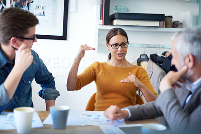 Buy stock photo Shot of a young businesswoman explaining something to her colleagues in a meeting