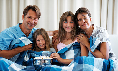 Buy stock photo Smiling family of four sitting on a sofa with bed sheet eating popcorn and watching a movie