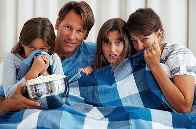 Buy stock photo Family of four eating popcorn and reacting to a horror movie