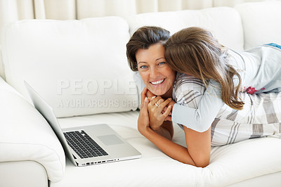 Buy stock photo Smiling mother lying on a sofa using laptop with daughter on top kissing her