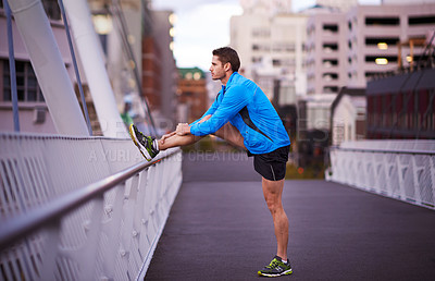 Buy stock photo Shot of a young man stretching before his run through the city streets