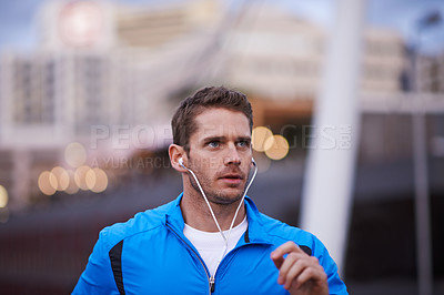 Buy stock photo Shot of a male jogger with earphones out for a run in the city