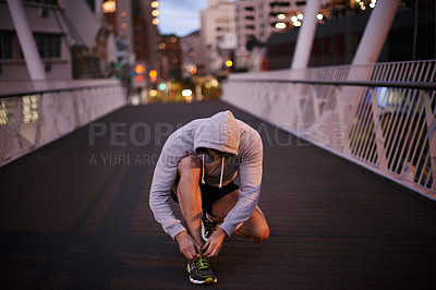 Buy stock photo Shot of a young man tying up his shoelaces before a run through the city
