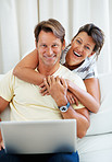 Couple using laptop and smiling