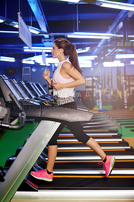 Buy stock photo Shot of a woman wearing earphones while working out on a treadmill at the gym