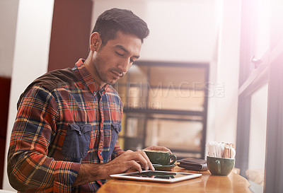 Buy stock photo Shot of a young man using a digital tablet in a coffee shop