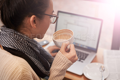 Buy stock photo A young woman working on her laptop while drinking coffee in a coffee shop