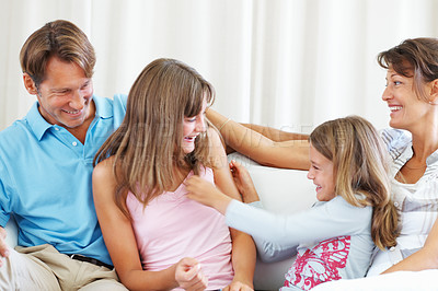 Buy stock photo Family of four sitting on a sofa and having fun together with young girl tickling her elder sister
