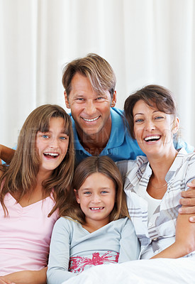 Buy stock photo Portrait of an attractive family sitting on a sofa and smiling