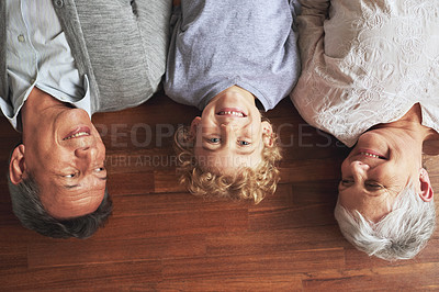 Buy stock photo High angle shot of a little boy lying between his grandparents on a wooden floor