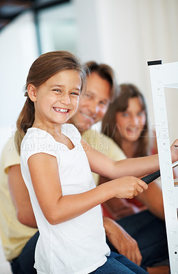 Buy stock photo Portrait of young girl using hammer while building a shelf with father and sister in background