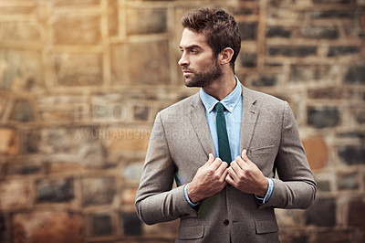 Buy stock photo Shot of a handsome and stylish young businessman in an urban setting
