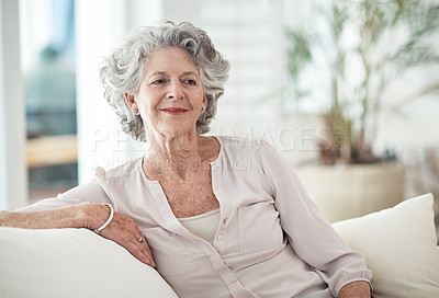 Buy stock photo Shot of a senior woman sitting on the sofa at home