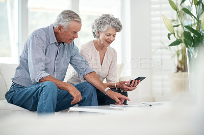 Buy stock photo Cropped shot of a senior couple working on their budget at home