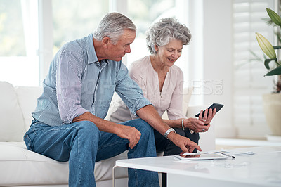 Buy stock photo Shot of a senior couple working on their budget at home