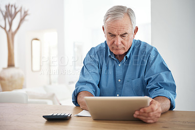 Buy stock photo Shot of a senior man working on his finances using a digital tablet