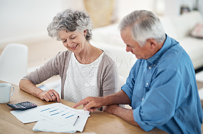 Buy stock photo Cropped shot of a senior couple reviewing their financial investments