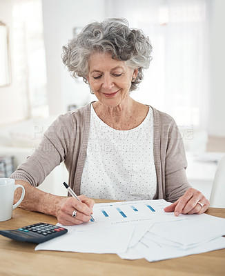 Buy stock photo Cropped shot of a senior woman reviewing her investments at home