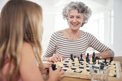 Buy stock photo Shot of a woman playing chess with her granddaughter